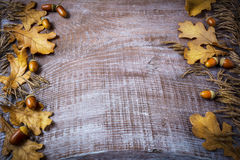 Frame of rye, acorn and fall leaves on dark wooden background stock photos