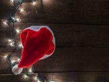 Frame of santa hat and Christmas lights on old wooden desk background and empty space for text. Top view with copy space.  royalty free stock images