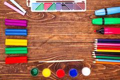 Frame of school supplies over a  retro wooden background. With c Stock Photo