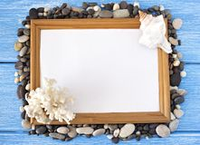 Frame of sea stones and seashells on a blue wooden background stock photography