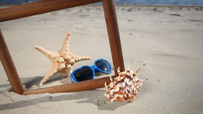 Frame with seashell, starfish and sunglasses on the beach Stock Photo