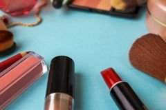 Frame from a set of female cosmetics from a lipstick, a highlighter, a pencil for lips, brushes, brushes, perfume, powder stock photos