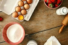 Frame set ingredients cooking strawberry pie cake wooden backgro. Frame of set ingredients for cooking strawberry pie or cake on wooden background. Eggs, flour Stock Photos