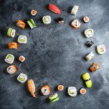 Frame with set of Japanese food on dark background. Sushi rolls, nigiri, raw salmon steak, rice and avocado. Flat lay. Top view. Frame with set of Japanese food stock photo