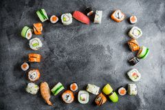 Frame with set of Japanese food on dark background. Sushi rolls, nigiri, salmon steak, rice and avocado. Flat lay. Top view. Frame with set of Japanese food on royalty free stock images