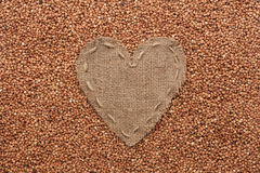 Frame in the shape of heart made of burlap with buckwheat Stock Image