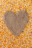 Frame in the shape of heart made of burlap with corn Royalty Free Stock Images