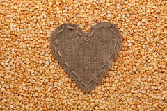 Frame in the shape of heart made of burlap with dry peas Royalty Free Stock Images