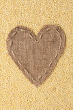 Frame in the shape of heart made of burlap with millet Royalty Free Stock Photo