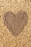 Frame in the shape of heart made of burlap with oats Stock Image