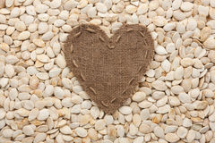 Frame in the shape of heart made of burlap with pumpkin seeds Royalty Free Stock Images