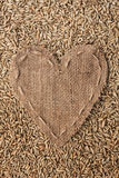 Frame in the shape of heart made of burlap with rye Stock Photos