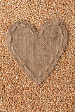 Frame in the shape of heart made of burlap with wheat Royalty Free Stock Photo