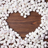 Frame in shape of heart of marshmallow on wooden background. Stock Photo