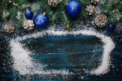 Frame with snow and Christmas decorations pine tree branches, cones, s blue Christmas toys on a wooden background. Place for text Royalty Free Stock Photos