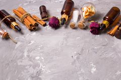 Frame with spa set bottles. On a vintage wooden tray: dry rose petals,orenge peel,aroma oils,sea salt,cinnamon, copy space Royalty Free Stock Photography