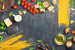 Frame of spaghetti with set of ingredients for cooking pasta. Frame of raw spaghetti with a set of ingredients for cooking pasta on a dark surface, top view Royalty Free Stock Photos