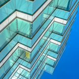 Frame Square Close up of an office building exterior against blue sky on a sunny day. Roller blinds on the windows provide shade and privacy to the rooms stock images