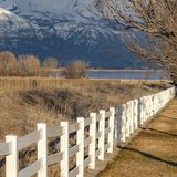 Frame Square Construction site near a lake viewed on the other side of a white picket fence. A snow caapped mountain and cloudy sky can be seen in the distance stock photo