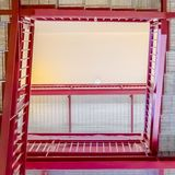 Frame Square Stairs with grated treads and bright red handrails viewed from below. The flight of stairs is inside a building with white ceiling and wall royalty free stock photo