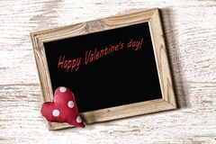 Frame of St. Valentine`s Day and homemade heart on a white wood texture board Stock Photo