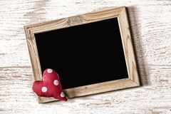Frame of St. Valentine`s Day and homemade heart on a white wood texture board Royalty Free Stock Photo