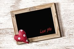 Frame of St. Valentine`s Day and homemade heart on a white wood texture board Stock Image