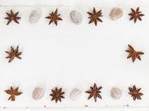 A frame of star anise and nutmeg on a rustic white table top Stock Photography