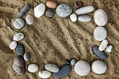 Frame of stones on a background of sand closeup Stock Photos