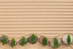 Frame of stones with green leaves zigzag on wavy sand. View from above Stock Photos