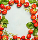 Frame of strawberries with green leaves and flowers on wooden background, top view Stock Images