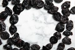 Frame of sweet dried plums on marble background. Top view with space for text. Healthy fruit royalty free stock image