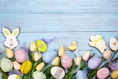 Frame of Sweets for celebrate Easter. Gingerbread in shape of easter bunny, chicken, colorful eggs and tulips. Blue background top view copy space royalty free stock photo