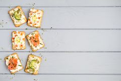 Crackers with cream cheese and various toppings. Appetizers on grey table. Healthy snacks, top view, flat lay Stock Photo