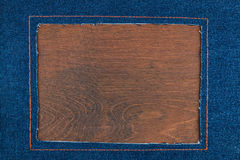 Frame for the text from a  jeans fabric with the stitched lines of an orange thread, on a dark wooden surface Royalty Free Stock Photos