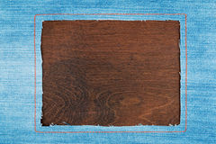 Frame for the text from a  jeans fabric with the stitched lines of an orange thread, on a dark wooden surface Stock Photography