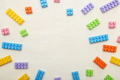 Frame of toy colored plastick bricks on light wooden background Royalty Free Stock Image