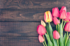 Frame of tulips on dark rustic wooden background. Spring flowers. Spring background. Valentine's Day and Mother's Day background. Top view Stock Photo