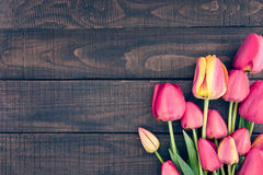 Frame of tulips on dark rustic wooden background. Spring flowers. Spring background. Valentine's Day and Mother's Day background. Top view