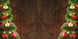 Frame of two christmas trees over wooden wall background Stock Photos