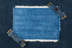 Frame with two straps jeans, lies on the dark denim Stock Photography
