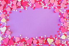 Frame of Valentines Day sweets and candy over purple Royalty Free Stock Photos