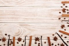 Frame of vanilla sticks, cinnamon, coffee beans on white wooden background with copy space for your text. Top view Royalty Free Stock Photography