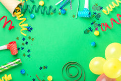 Frame from various celebratory items on green background Royalty Free Stock Photo