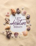 Frame of various seashells on sandy beach, let adventure begin inscription royalty free stock image