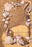 Frame from various shells on sand and old map Royalty Free Stock Images