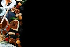 Frame of various wine snacks: blue cheese, brie, grapes, figs, honey, fruits and nuts isolated on black background. Top view royalty free stock photography