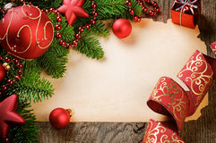 Frame with vintage paper and Christmas decorations. On wooden background Royalty Free Stock Photos