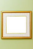 Frame on wall. Empty gold frame on green museum wall with isolated center Royalty Free Stock Images