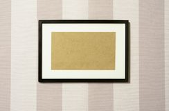 Frame on wallpaper 03. Black wooden frame on striped wallpaper. Cardboard rectangle can easily be replaced in PS by any other image Stock Photos